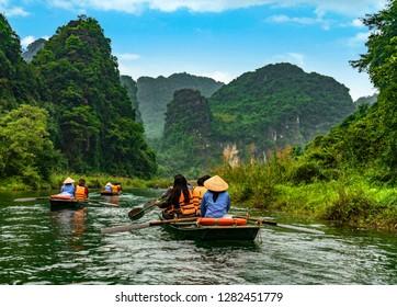 Unrecongnisable people take boat on river at Trang An at Ninh Binh, Vietnam