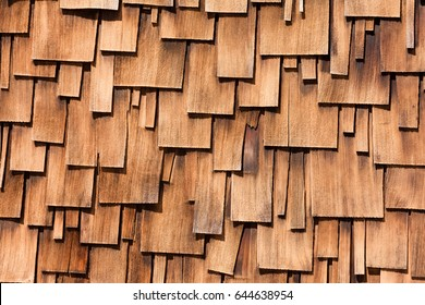 Unregular pattern of overlapping Western Red Cedar shingles natural organic wooden wall siding for residential buildings