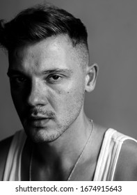 Unretouched portrait of young male close up with undercut hair style. Half lighted portrait. Black and white style. Dressed in white singlet , gray background