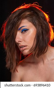 Unretouched portrait of a young pretty caucasian brunette girl posing in a studio on black background with bright orange backlight. She has messy hair and bright blue eye liner and beige lip gloss.