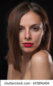 Unretouched, raw studio portrait of a young and pretty caucasian brunette girl with red lipstick, shot of black background with backlight.