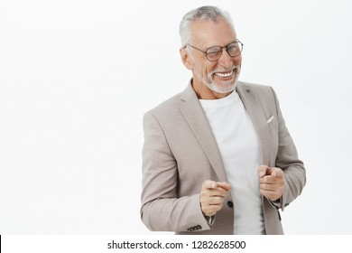 Unretouched studio shot of charming elegant and happy charismatic mature businessman in glasses and suit with bad teeth winking joyfully pointing delighted at camera as if hinting against grey wall