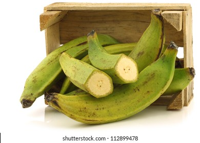 unripe baking bananas (plantain bananas) and a cut one  in a wooden crate on a white background