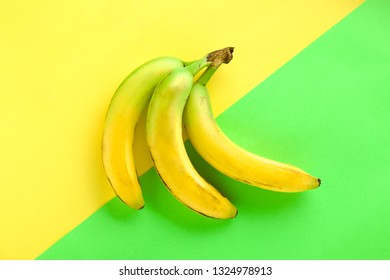 Unripe Bananas on Yellow and Green Background