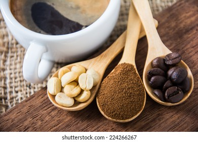 unroasted, roasted and ground coffee in wooden spoons