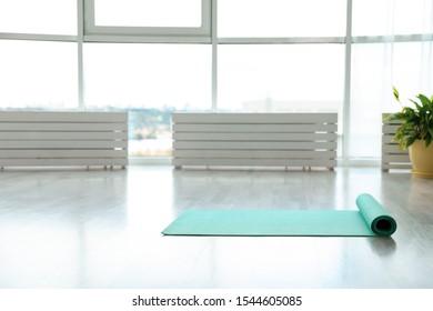 Unrolled light blue yoga mat on floor in room