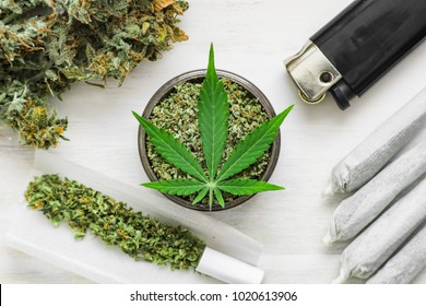 unrolled weed Joint and a grinder with crushed weed Leaf of cannabis, buds of marijuana, on a white wooden background top view medical