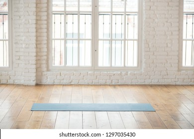 Unrolled yoga mat lying in empty light fitness studio on wooden floor, unfolded sport equipment prepared for training, modern pilates loft room ready for workout session. Healthy life concept