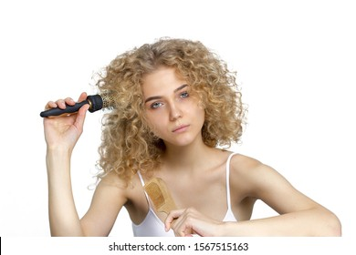Unruly hair. Woman combs curly hair