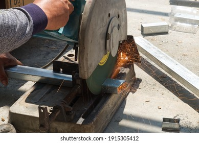 Unsafe Worker Cutting Metal Construction with no Protection Uniform with Electric Wheel Fabric Cutting Machine in the Construction Site.