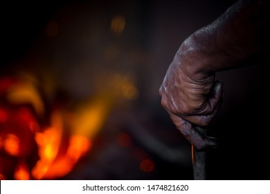Unsafe worker hands. A local steel machine parts making yard worker melting scrap on hot furnace.