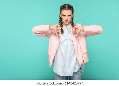 unsatisfied dislike portrait of beautiful cute girl standing with makeup and brown pigtail hairstyle in striped light blue shirt pink jacket. indoor, studio shot isolated on blue or green background.