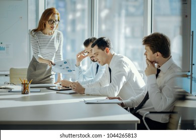 Unsatisfied with performance. Pretty young female boss holding printouts with inaccurate research results and reprimanding her employees for a poor performance