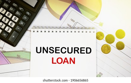 Unsecured loan on notepad with calculator, coins, graphics on financial report. Business and financial concept - Shutterstock ID 1906656865