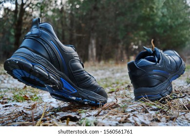 Unseen legs in empty couple of sport black running shoes in motion running or walking on path with autumn grass and snow in the Park on background of coniferous forest. Bottom side view on sole