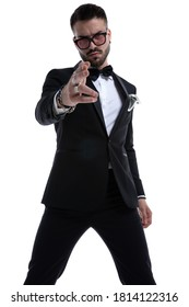 unshaved dramatic man in tuxedo pointing fingers and making gun gesture isolated on white background