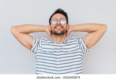 Unshaved handsome male model wearing trendy round mirror sunglasses and striped casual shirt posing against white studio background enjoying good summer weather. People, lifestyle and emotions concept