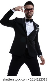 unshaved young man in tuxedo pointing fingers to head and posing isolated on white background