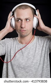 unshaven attractive young man listening to music in headphones with a sullen expression on his face on a black background
