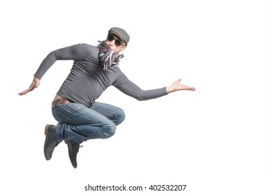 Unshaven bald man wearing a cap, jeans, sunglasses and scarf jumping. Isolated