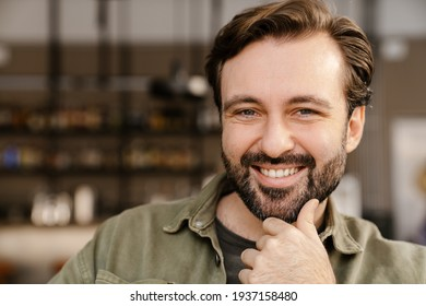 Unshaven happy man smiling and looking at camera while sitting in cafe