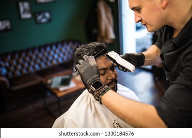 Unshaven man being clipped with professional electric shearer machine in barbershop. Male beauty treatment concept. Indian guy trim beard and mustache at barber shop salon