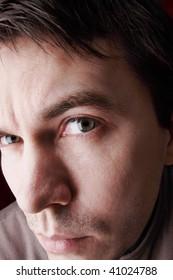 Unshaven man in casual wear posing in the studio. Dark background. Aggressive and attentive.