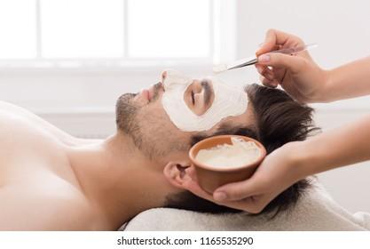 Unshaven man getting facial nourishing mask by beautician at spa salon