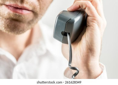An unshaven man listening to a telephone conversation holding the receiver in his hand , focus to the receiver.