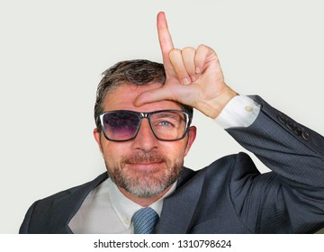 unshaven and werid businessman in weird broken nerdy glasses and stupid smile doing loser sign with L fingers signal on forehead with funny ridiculous expression in unsuccessful geek concept