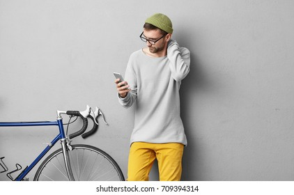 Unshaven young European guy wearing stylish glasses and hat touching his neck while reading important news or text message on generic smart phone, standing at grey wall with fixed gear bike
