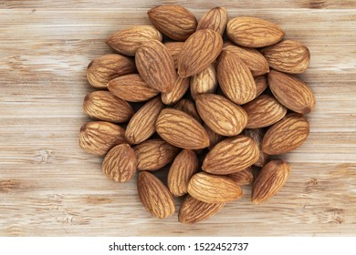 Unshell almonds lie in a heap in the center on a brown wooden background, top view, close-up