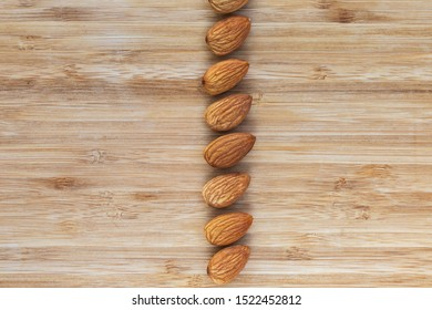 Unshell almonds lie in a vertical line in the center on a brown wooden background, left and right - empty space, top view, close-up
