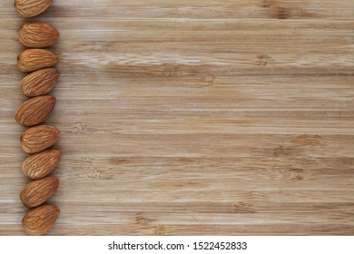 Unshell almonds lie in a vertical line on a brown wooden background on the left, on the right is an empty place, top view, close-up