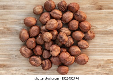 Unshelled hazelnuts lie in a heap in the center on a brown wooden background, top view, close-up
