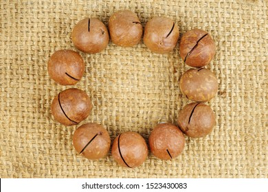 Unshelled macadamia nuts on jute background