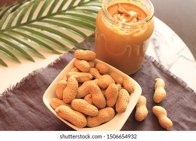 Unshelled peanuts in a porcelain bowl and a jar of peanut butter on a braided mat.