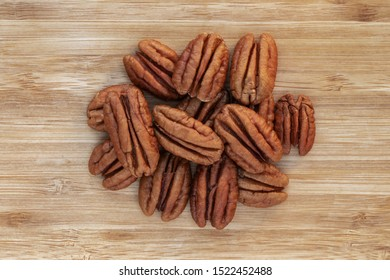 Unshelled pecans in a center bunch on a brown wooden background, top view, close-up
