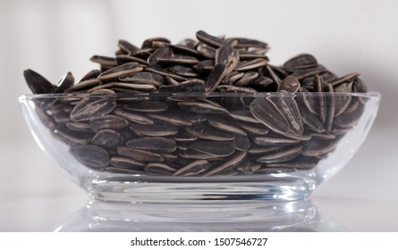 Unshelled sunflower seeds in oval glass bowl on white surface. Organic snack