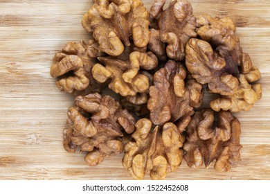 Unshelled walnuts lie in a pile in the center on a brown wooden background, top view, close-up