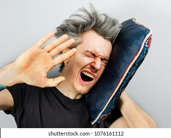 Unshorn and unshaven young guy with piercings on his face sleeps on the pillow and yawn, on gray background.
