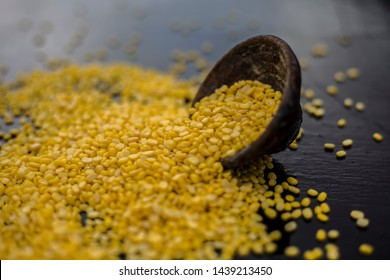Unskinned split mung dal or moong dal in a black colored clay bowl on the black wooden surface used for various dishes. Also referred to as green gram, maash, or moong or unskinned mung beam.