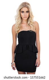 Unsmiling blonde model in black dress posing looking at camera on white background