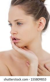 Unsmiling brunette model posing holding her head on white background