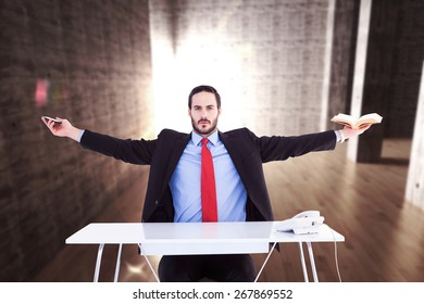 Unsmiling businessman sitting with arms outstretched against abstract room