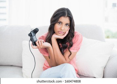 Unsmiling cute brunette sitting on couch holding controller in bright living room