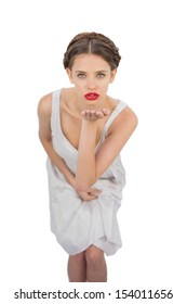 Unsmiling model in white dress blowing a kiss at camera on white background