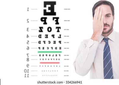 Unsmiling patient looking at camera with one eye against eye test