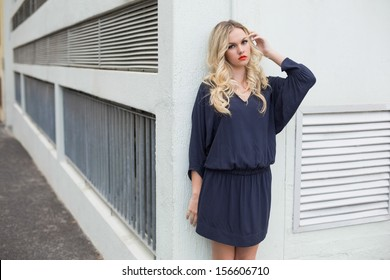 Unsmiling sexy blonde wearing classy dress posing outdoors against building