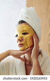 Unsmiling woman in bathrobe with golden gel sheet mask on her face looking at herself in mirror, skincare and anti-aging treatment concept